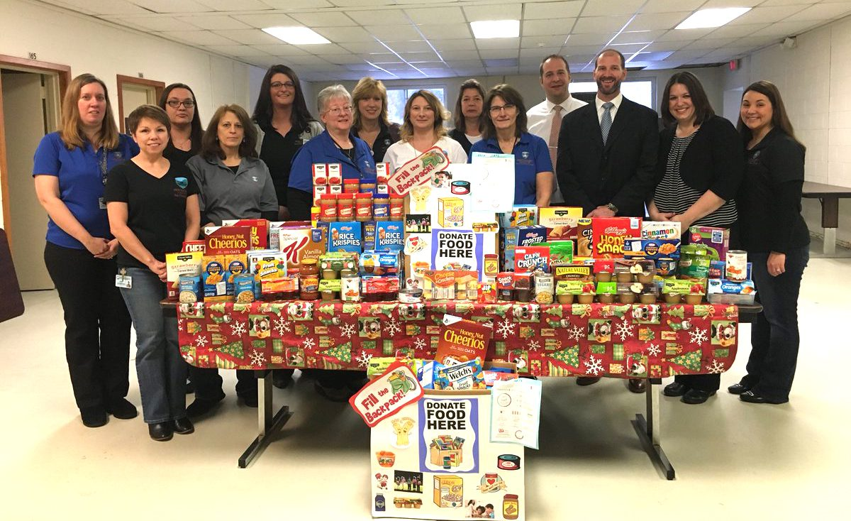public health department employees, school administrator and social worker stand behind table filled with canned goods