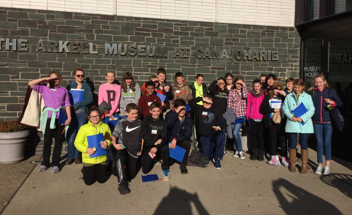 group of students stand outside museum