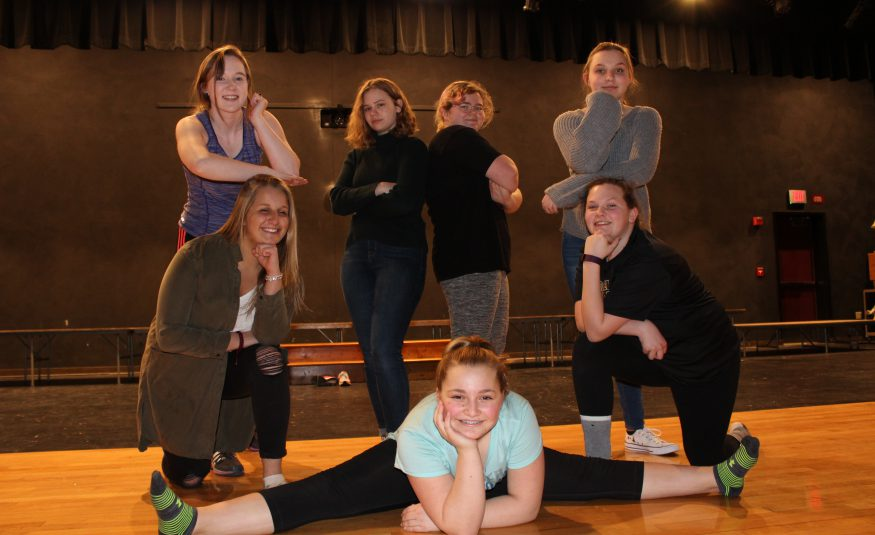 student actors pose in a group on the stage in an auditorium
