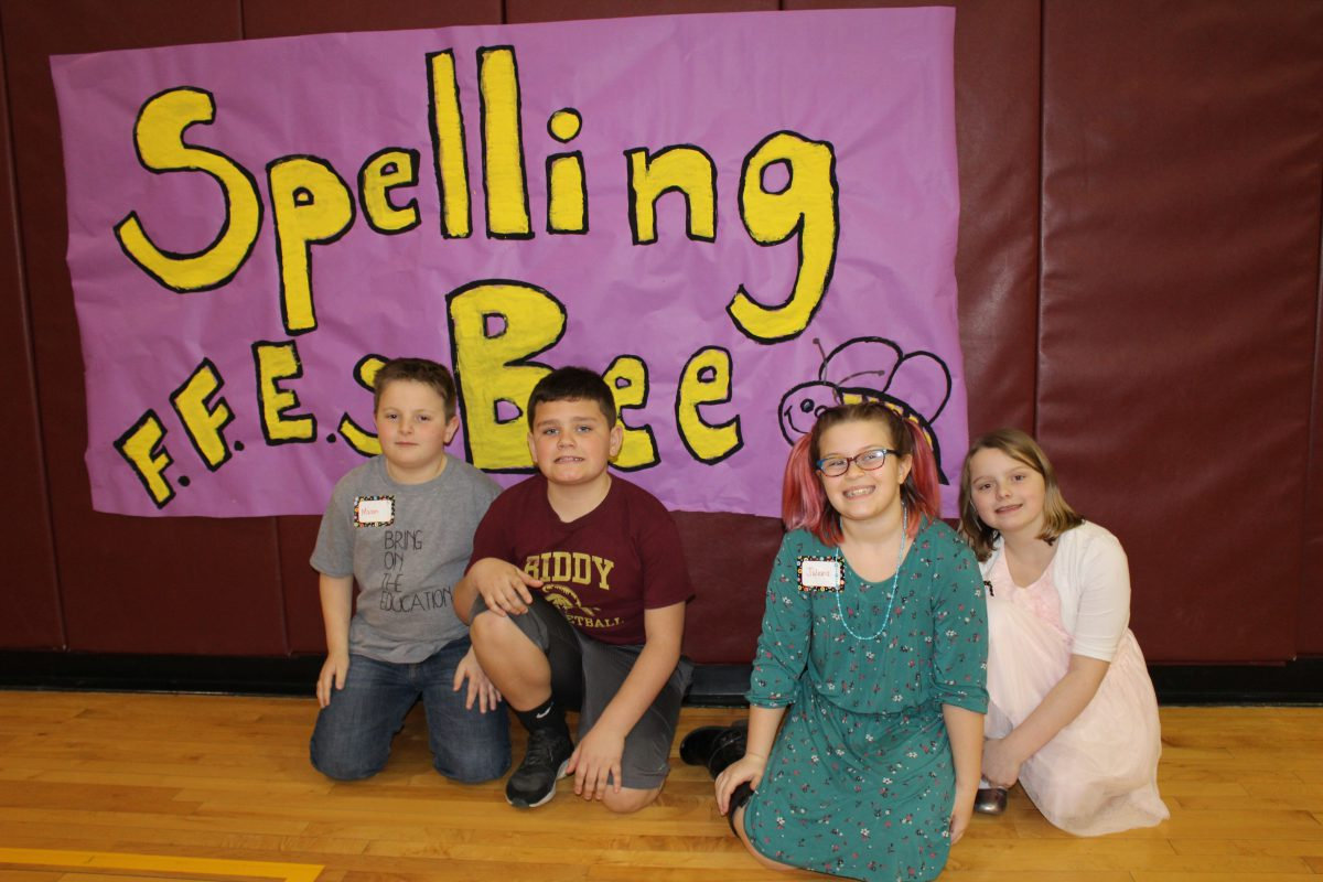 Four third graders sit in front of 'spelling bee' sign