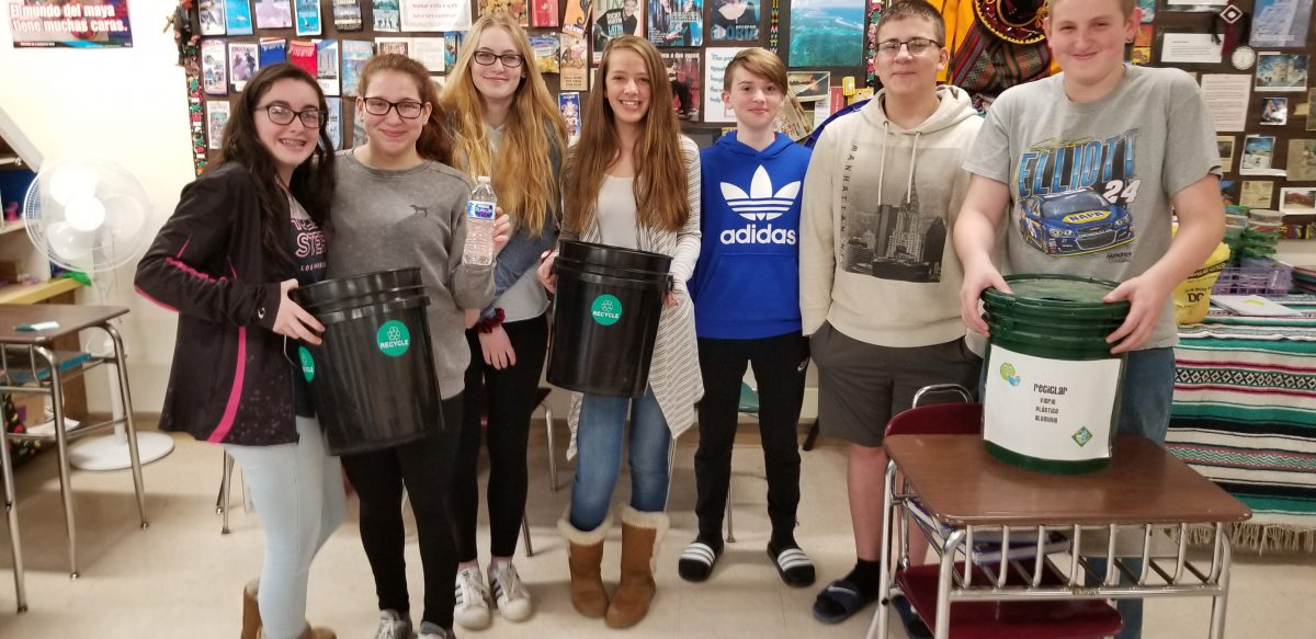 seven middle school students hold recycling buckets