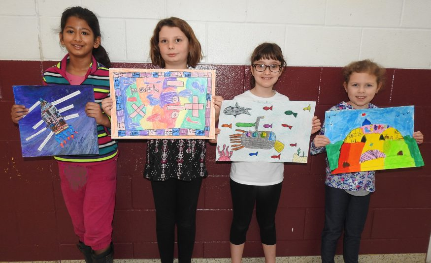 four elementary students hold artwork entered in a Crayola contest