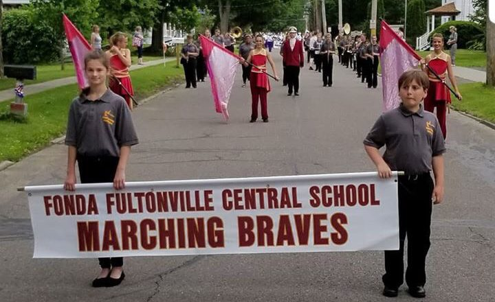 two students stand in the street with a sign that says Fonda-Fultonville Central School Marching Braves, with color guard behind them