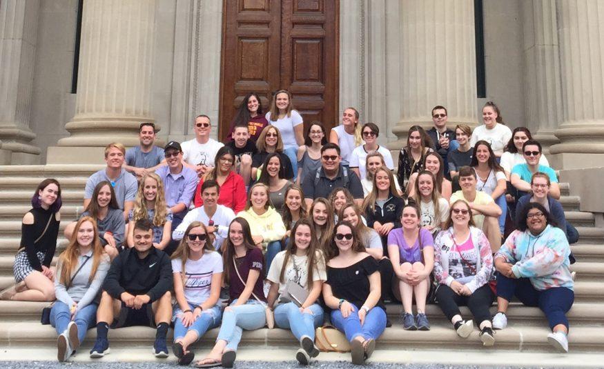 group of 40 high school students and three teachers sit on steps of Vanderbilt mansion