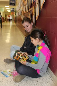 high school student and elementary student seated on floor in hallway while reading