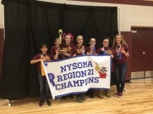 """students hold a trophy, a """"champions"""" banner and blue ribbons"""