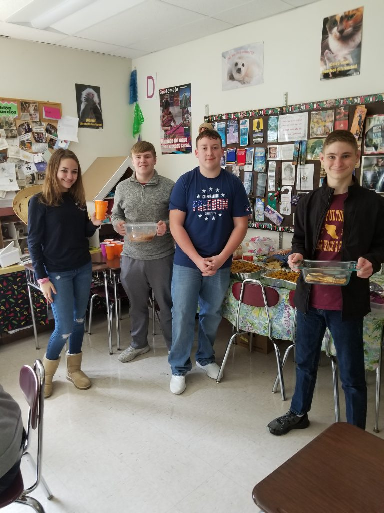 four high school students hold dishes of Latin cuisine