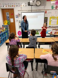 high school teacher stands with first grader at the front of an elementary classroom