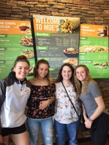 four high school students stand in front of menu at Moe's Southwest Grill
