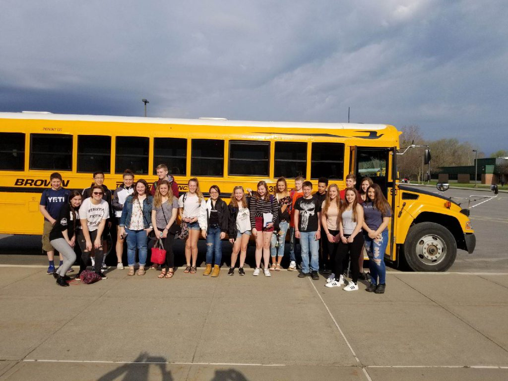 large group of high school students pose in front of a school bus