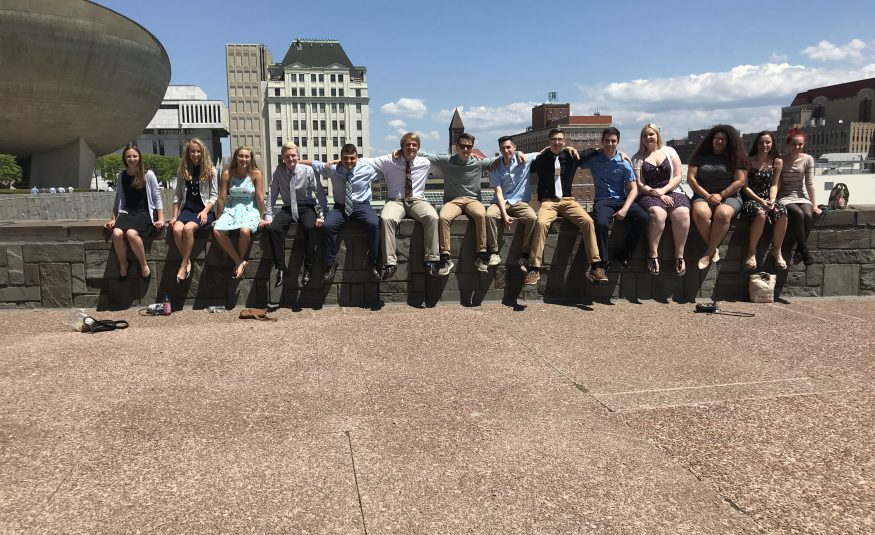 high school students seated on a roof ledge at the NYS Capitol building