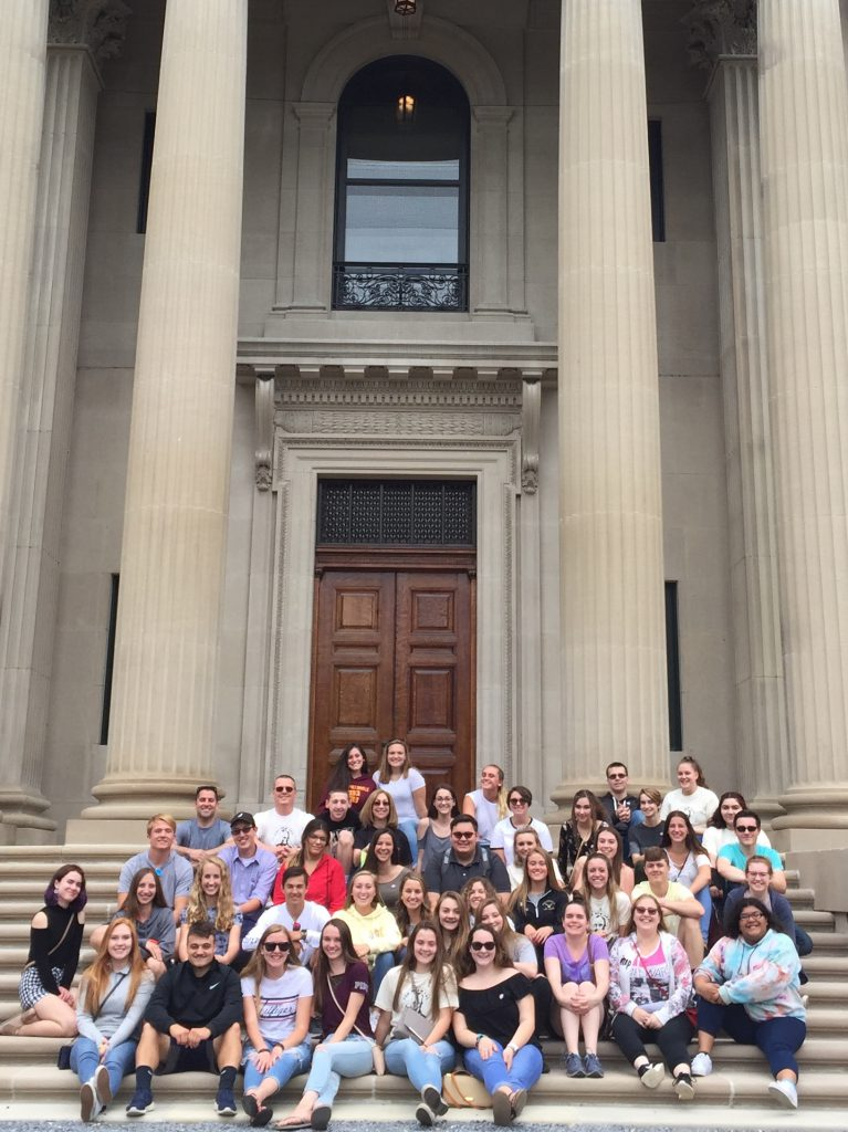 group of 40 high school students and three teachers sit on steps of Vanderbilt mansion