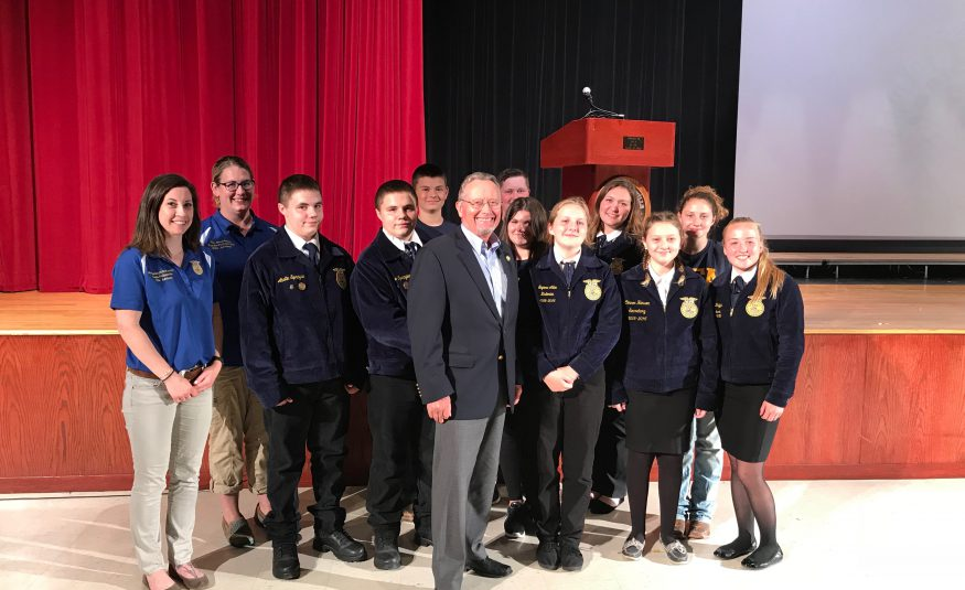 state official poses in high school auditorium with FFA students and advisors