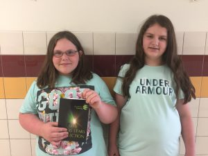 Two middle school students stand in school hallway. One is holding a book.