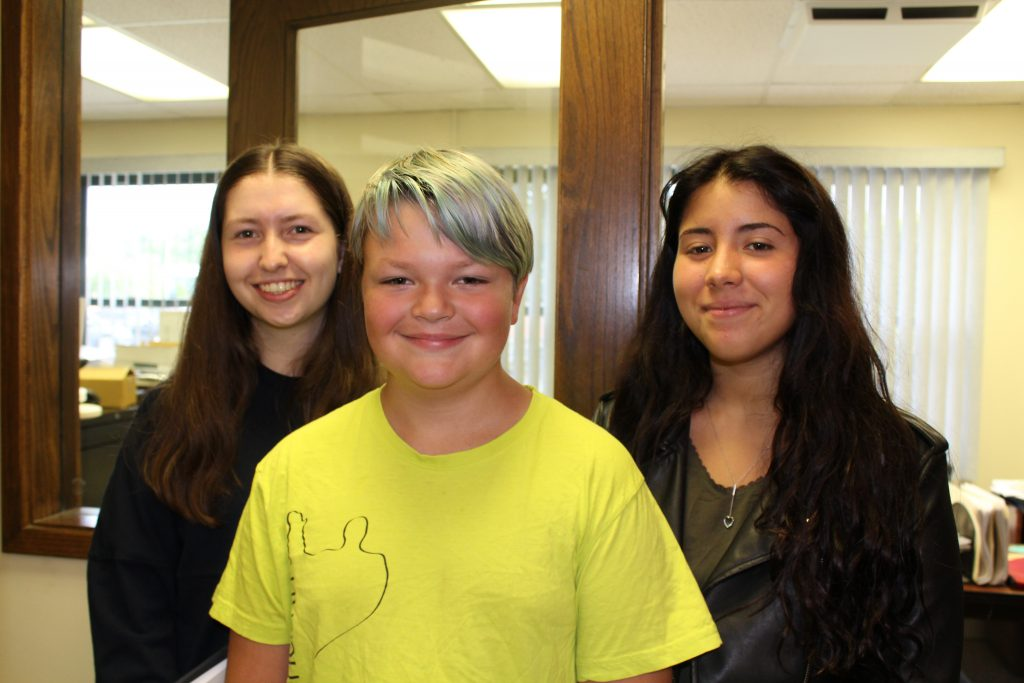 A middle school student is flanked by two high school-aged exchange students