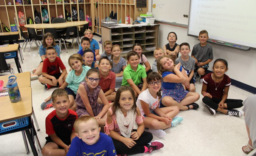 class picture of third grade class seated on carpet in classroom