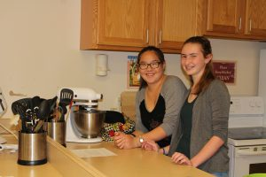 Two high school students mix cookies in a standup mixer in a home and careers classroom