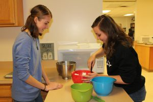 Two high school students mix cookies in a bowl with a spoon in a home and careers classroom