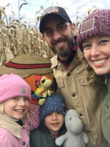 Two parents and their two children pose for a selfie in a corn field