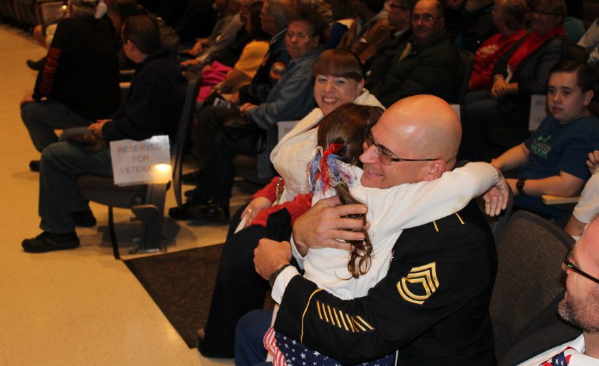 serviceman in army uniform hugs his daughter in school auditorium