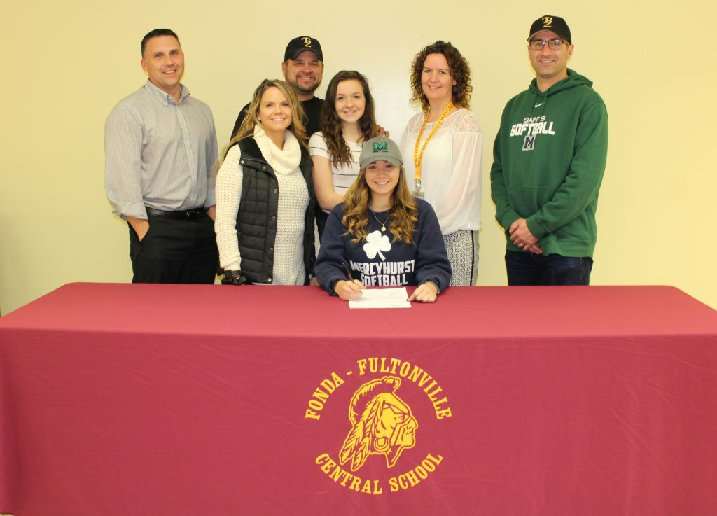 student athlete seated at table signs a piece of paper while surrounded by her coach, athletic director, parents, sister and family friend