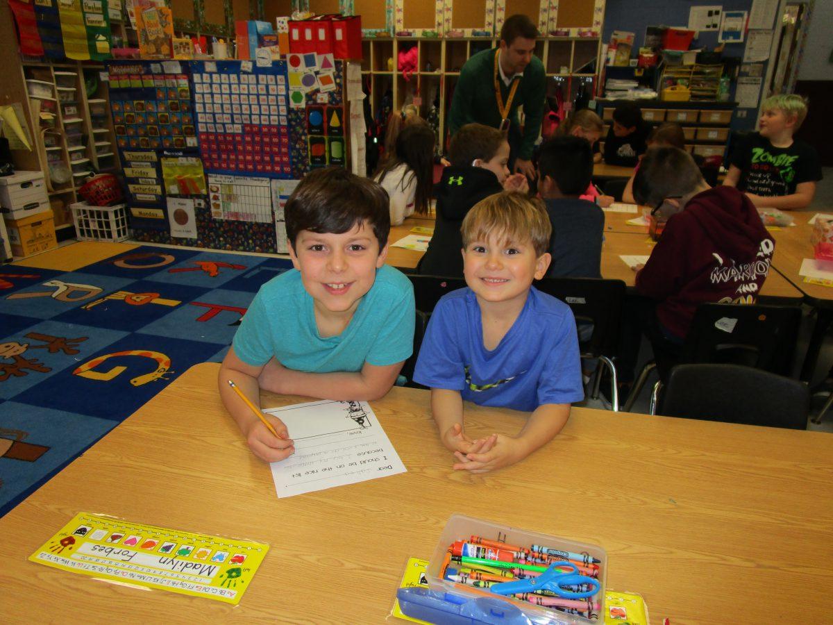 Fourth graders help kindergarten students write letters to Santa