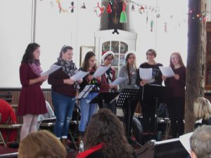 seven high school students sing at the front of a former church