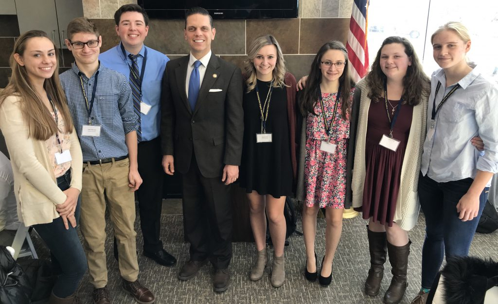 seven high school students in dress clothes with a state assemblyman