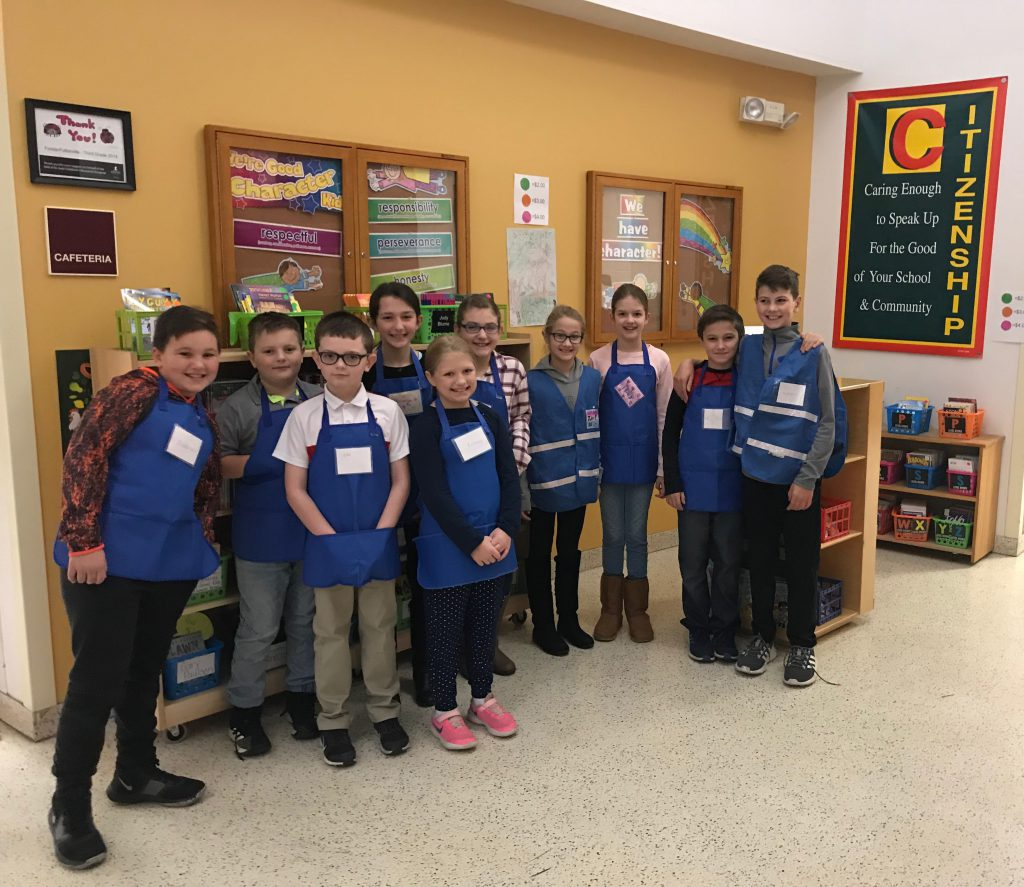 group of fourth graders wearing blue aprons stand in front of bookstore at an elementary school