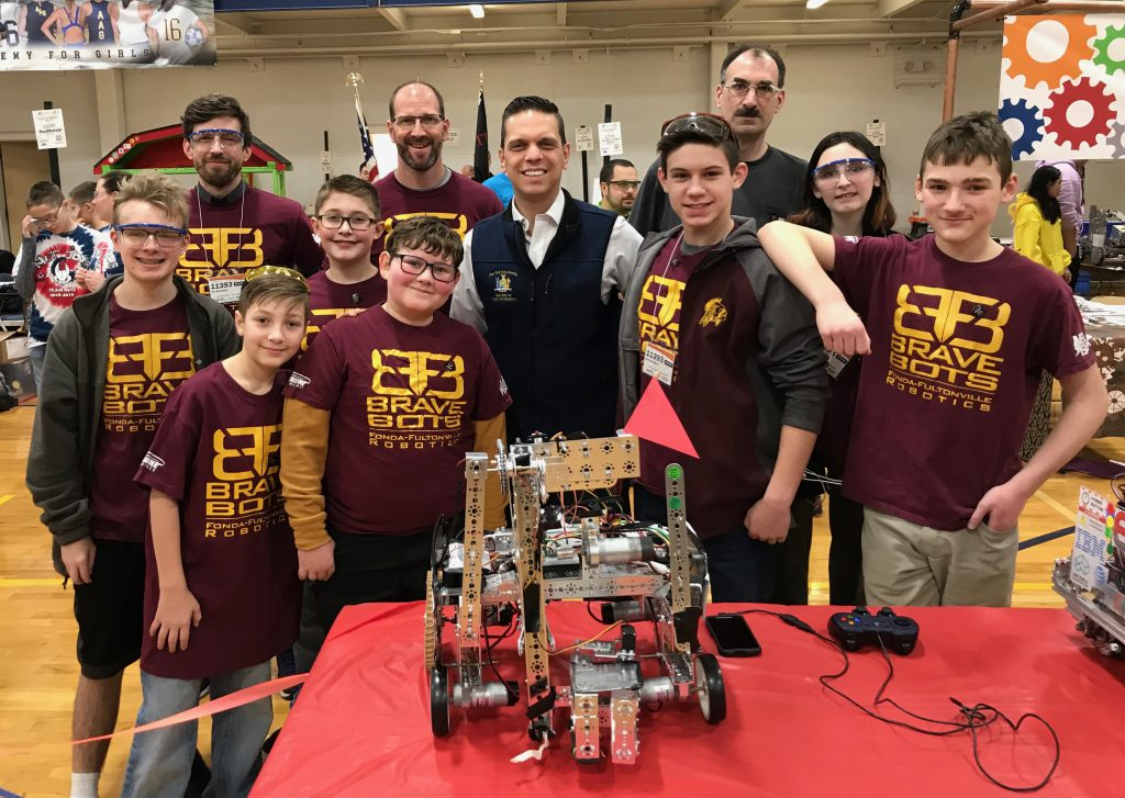 group of middle and high school students, an assemblyman, a school superintendent and robotics team coach wearing maroon 'Brave Bots' T-shirts stand before a robot on a table
