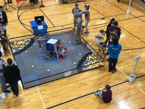 teams stand around a robotics court on a mat in a gymnasium
