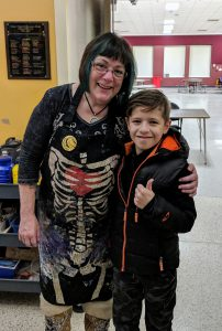 art teacher stands with arm around student who gives thumbs up