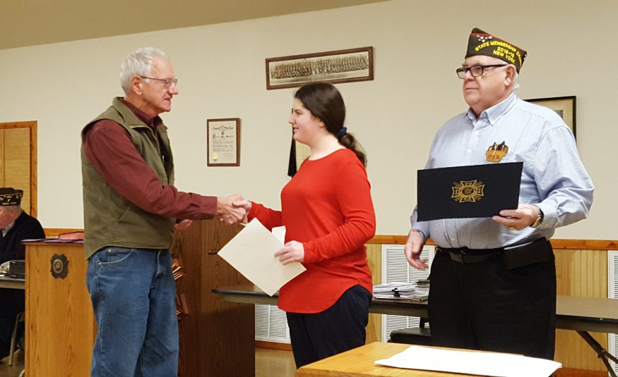 middle school student shakes hands with a representative of the VFW while a second representative, at right, holds a certificcate