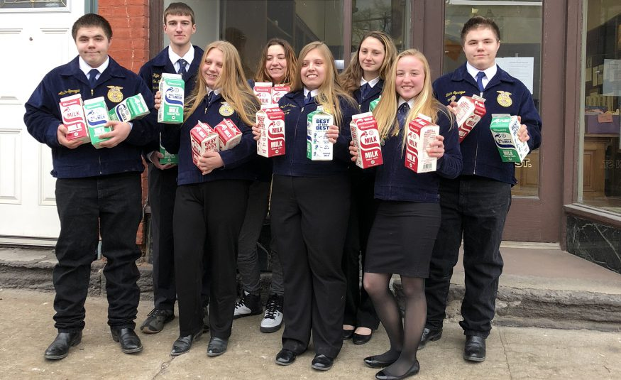 group of high school students wearing FFA jackets hold half gallons of milk in front of a food pantry