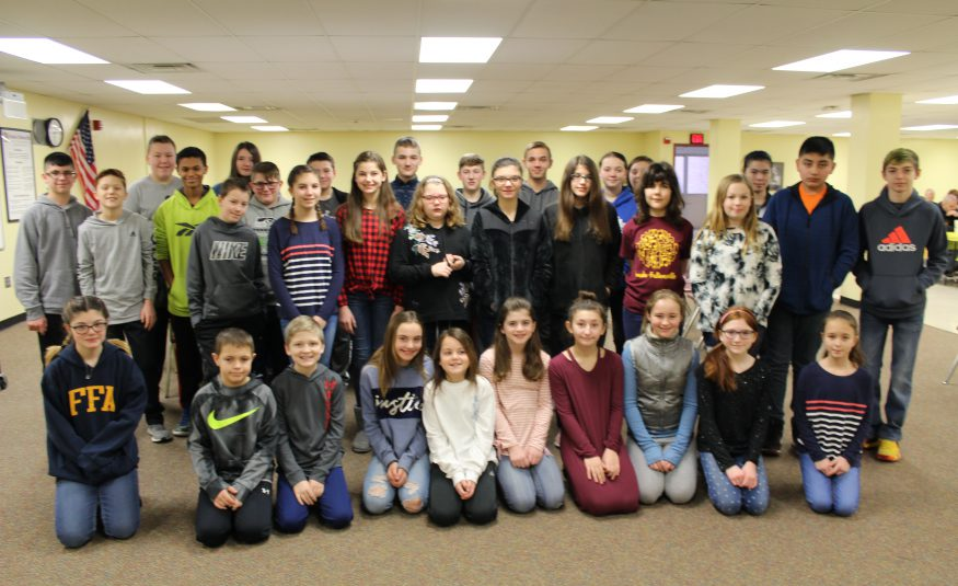 three rows of middle school students stand in the multi-purpose room