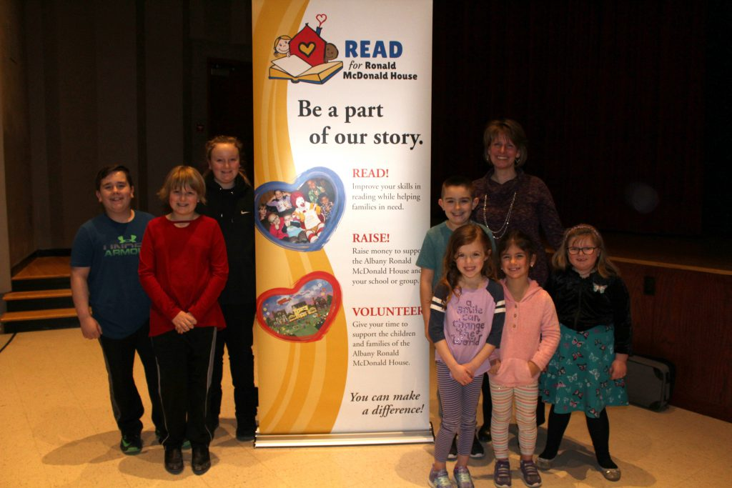 a group of elementary and middle school students stand next to a poster for the Read for Ronald McDonald House with its program coordinator