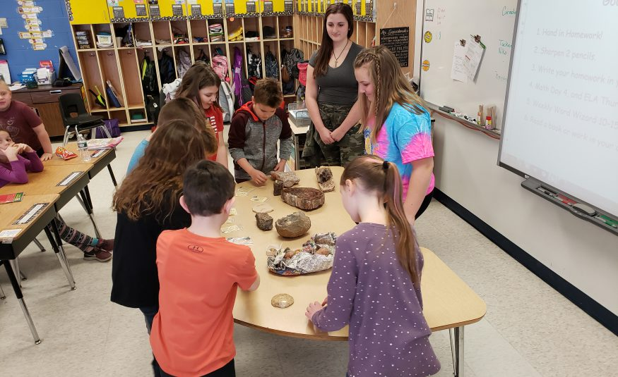 elementary students observe fossil collection on table with high school students