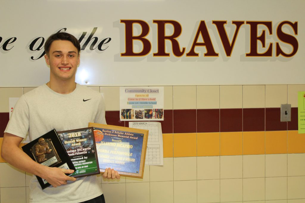 high school boy standing in front of braves sign holding three award plaques
