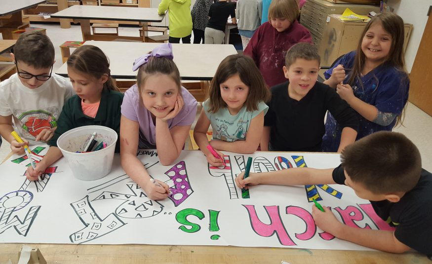 """seven elementary students make a banner that says """"march is youth art month"""""""