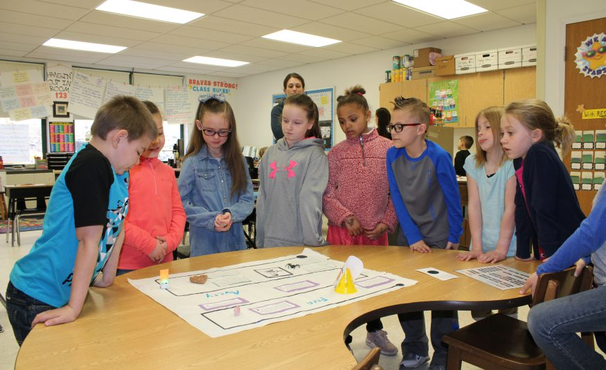 group of eight students stand around a table and look at a decorated storyboard in an elementary classroom