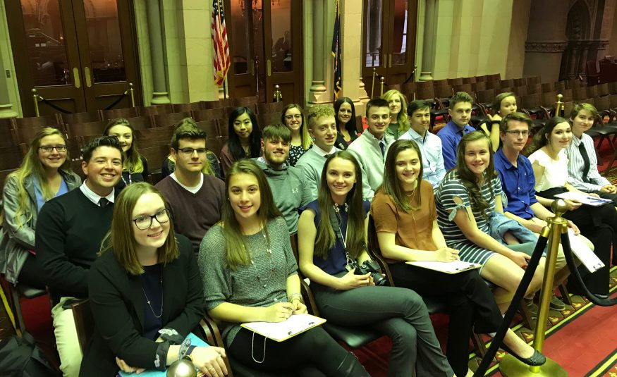 Two dozen participation in government students are seated at the state capitol