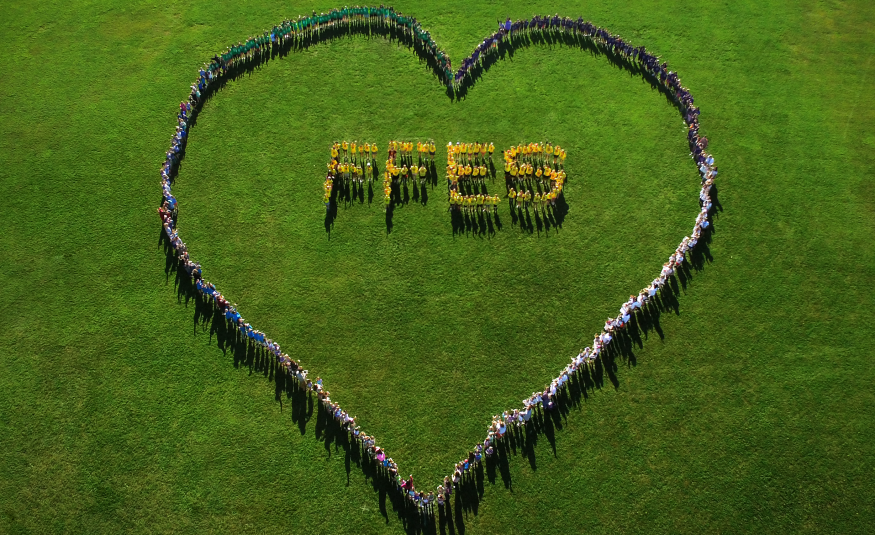 aerial view of hundreds of students making the shape of a heart and the letters FFES