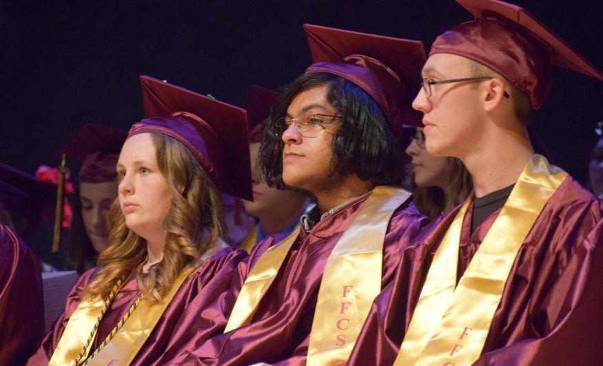 several students sit on stage