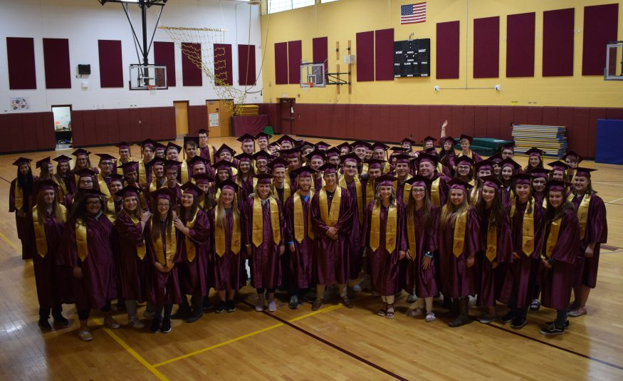 The class of 2019 stands in a gym