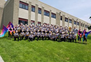 A marching band poses for a photo in front of a building