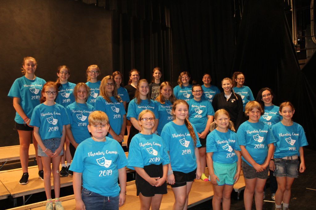 Group of students wearing blue theater camp t-shirts stand on risers on a stage in a school auditorium