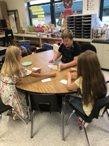three students seated at table in elementary classroom build a card tower