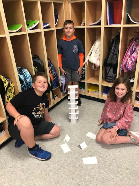 three students stand before cubbies behind a card tower they made in an elementary classroom