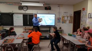 machinist points to a digital map in front of a sixth grade classroom