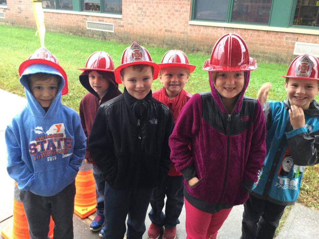 group of six students wearing plastic firemen hats outside of an elementary school
